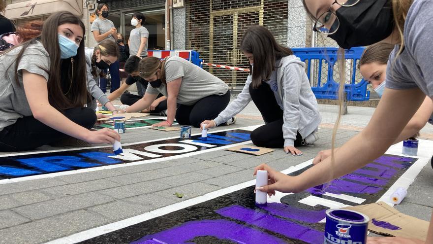 Adolescentes pintan en Lena un paso de peatones por el Día del Orgullo
