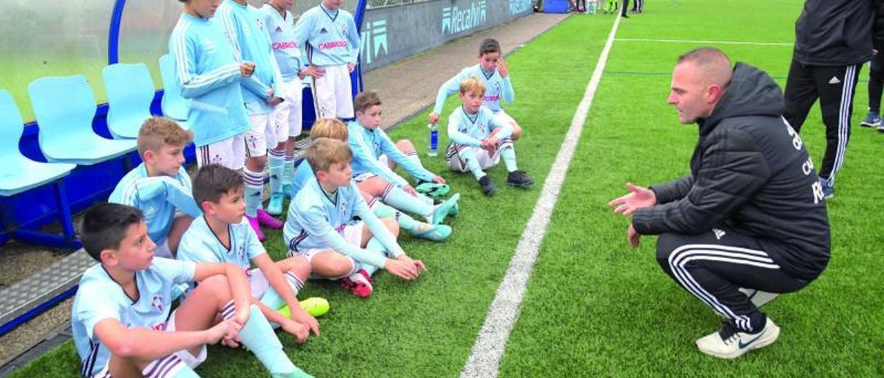 Niños de la cantera del Celta atienden a las explicaciones de su entrenador. // EUGENIO ÁLVAREZ