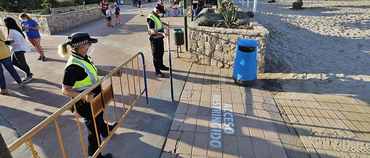 La policía de Sagunt en el momento de cerrar la playa del Port. | DANIEL TORTAJADA