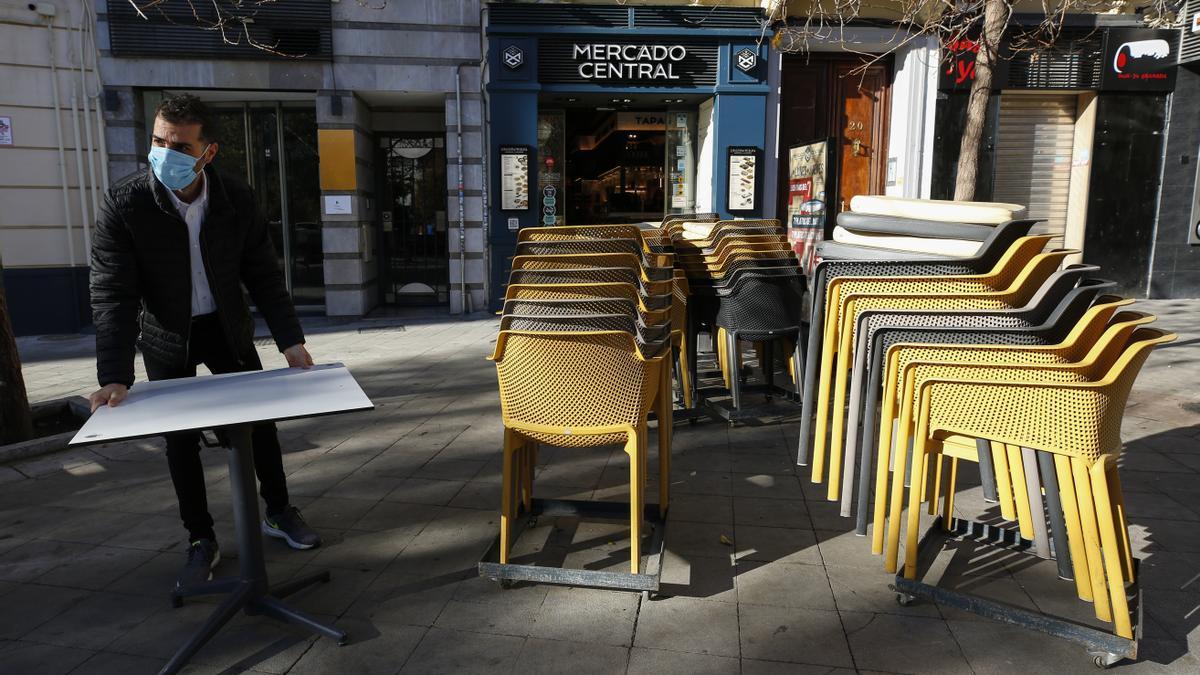 Camareros limpiando y poniendo las mesas en las terrazas de los bares.