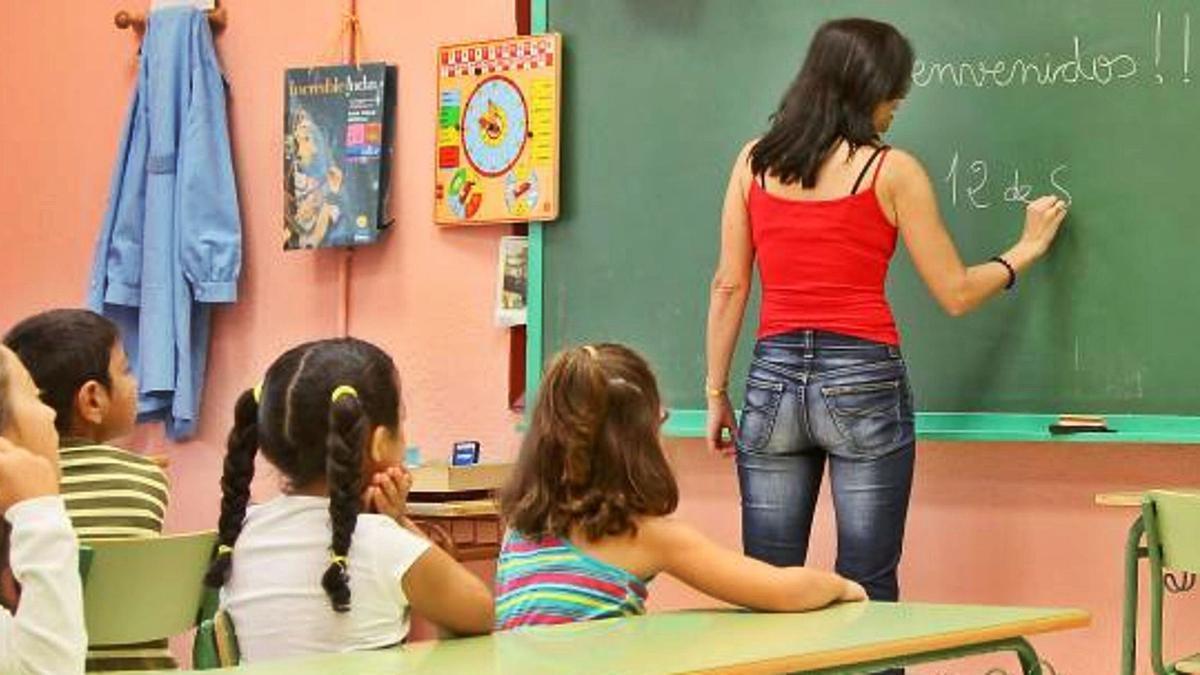 Una profesora escribe en la pizarra durante una clase.