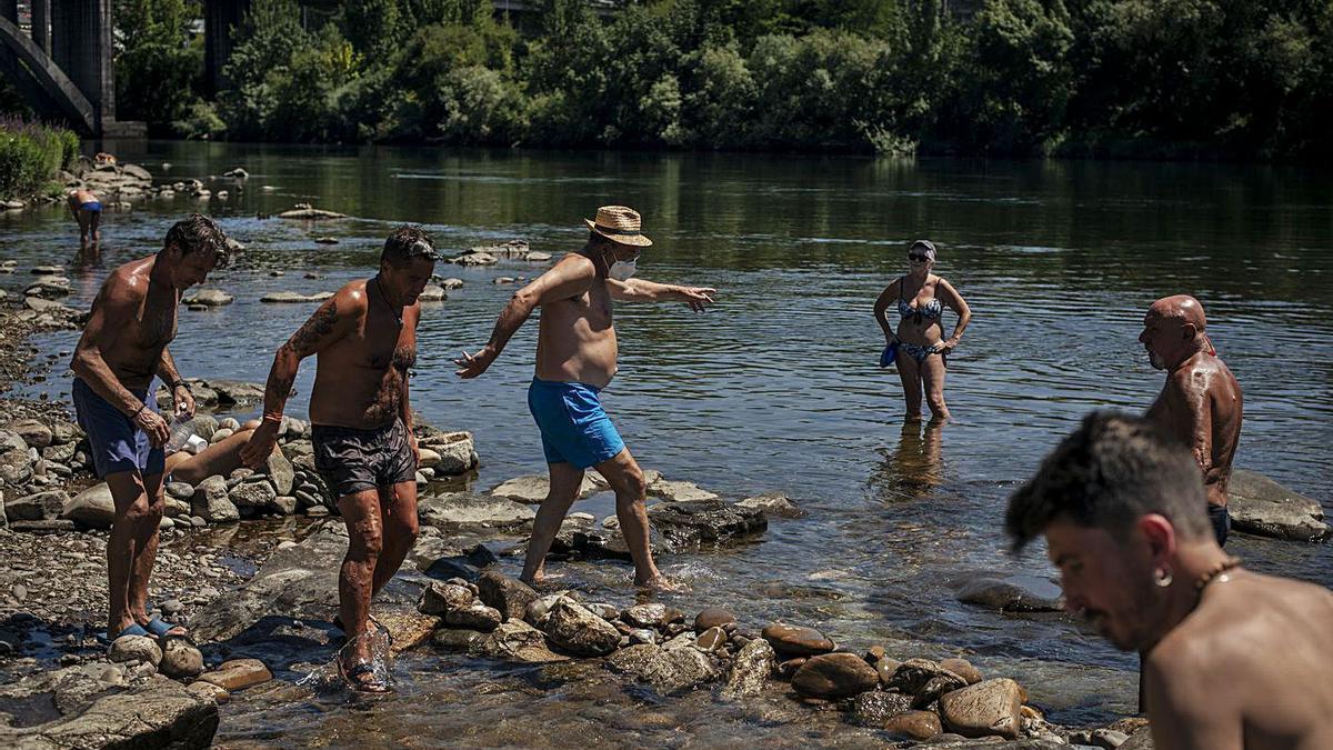 Varias personas se refrescan en el Miño, ayer, en una jornada de calor abrasador.     // BRAIS LORENZO