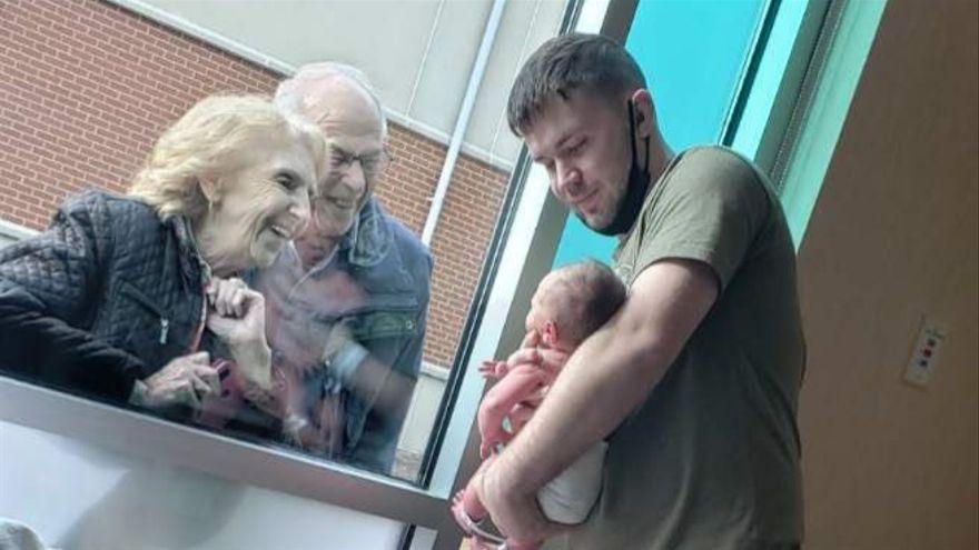 La tierna imagen de unos abuelos conociendo a su nieto recién nacido a través de una ventana