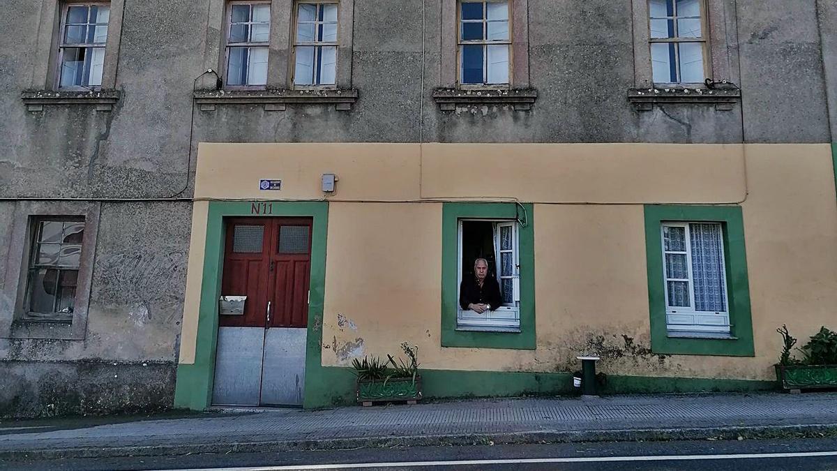 Felisardo Barros, vecino de Betanzos, asomado en su vivienda, única habitada del edificio.   | // LA OPINIÓN