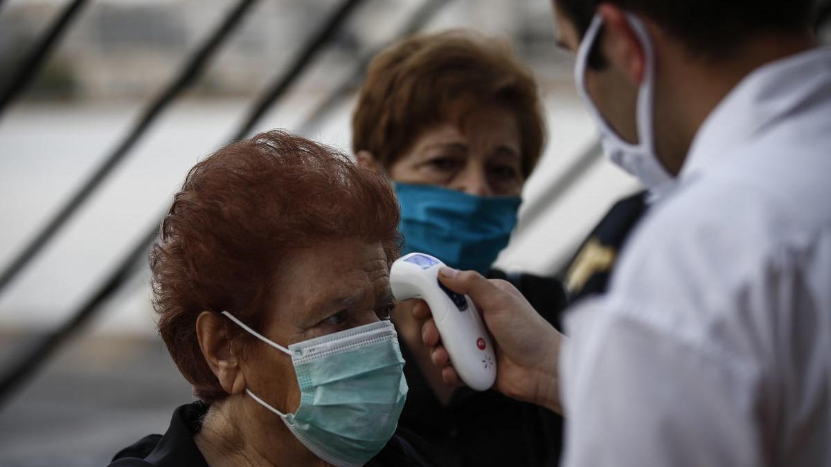 Un sanitario toma la temperatura en el puerto de Piraeus.