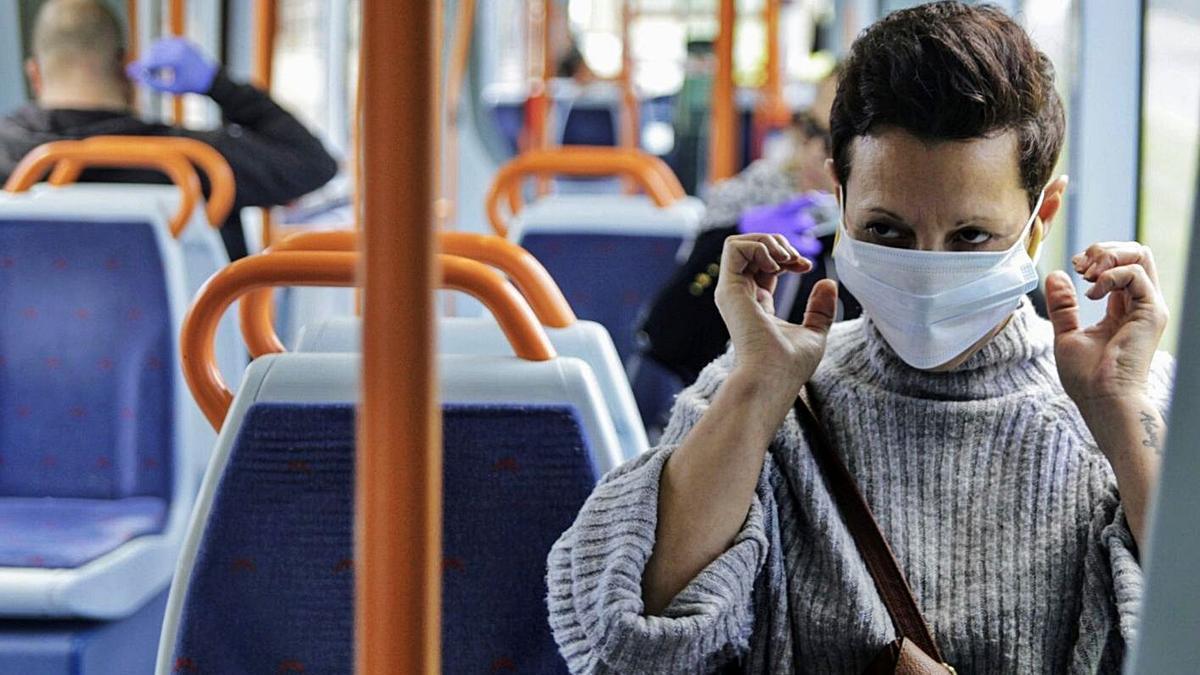 Una usuaria se coloca la mascarilla en el interior del tranvía.     DELIA PADRÓN
