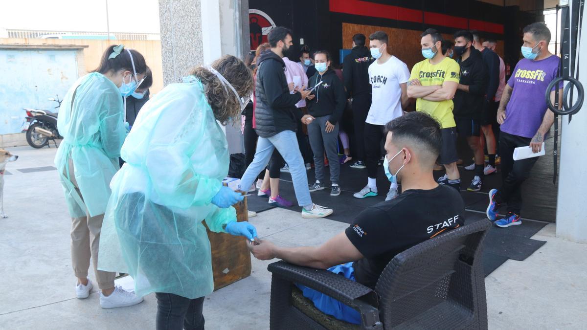Una de les infermeres de Freecov agafant sang d'un client d'un grup de crossfit, davant del gimnàs