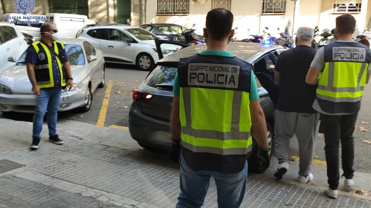 Los policías custodian al presunto falsificador detenido en la operación.