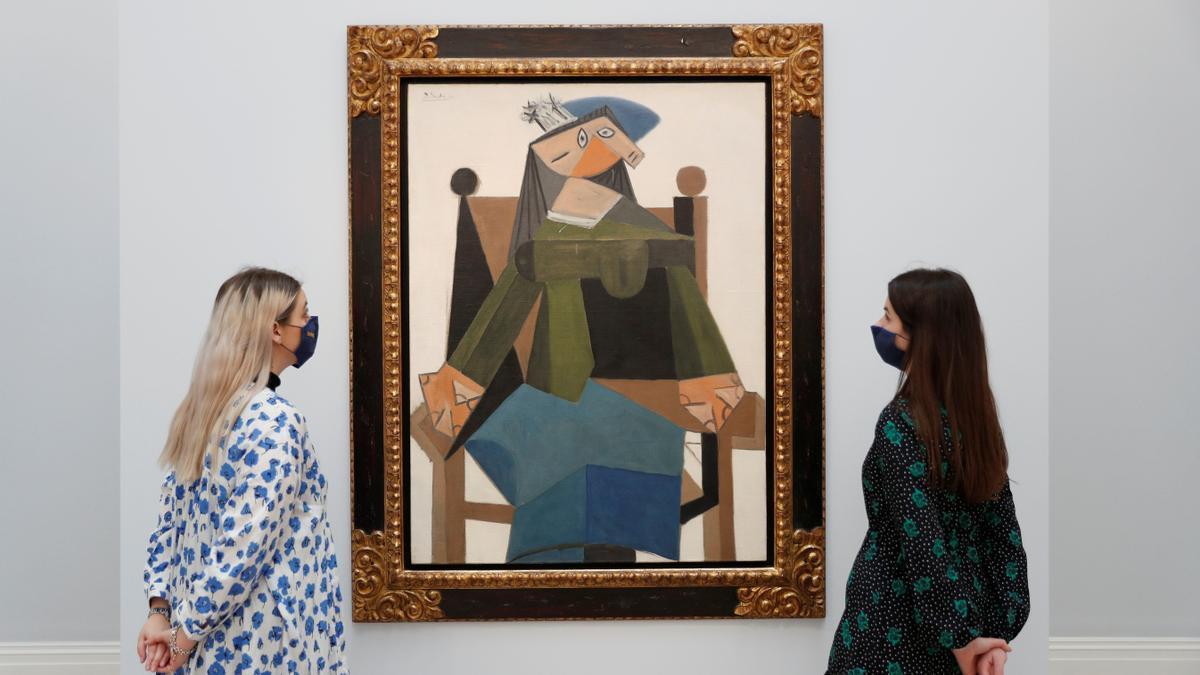 Trabajadores de Sotheby's observan 'Femme Assise Dans Un Fauteuil', de Pablo Picasso.