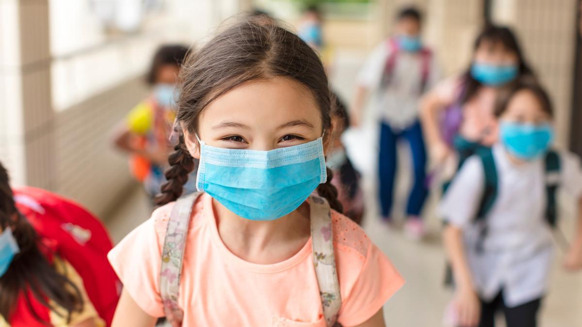 Una niña con mascarilla en el colegio.