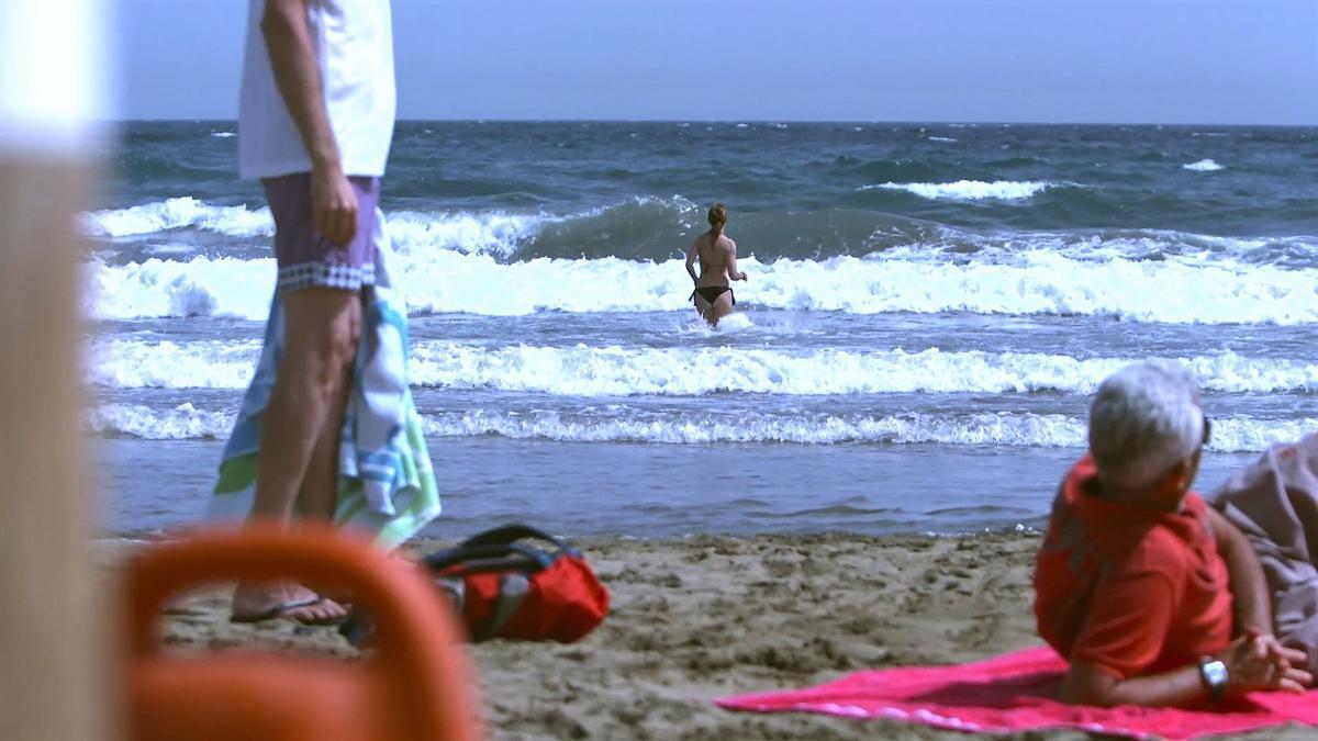 Una mujer entra en el agua con mal estado del mar
