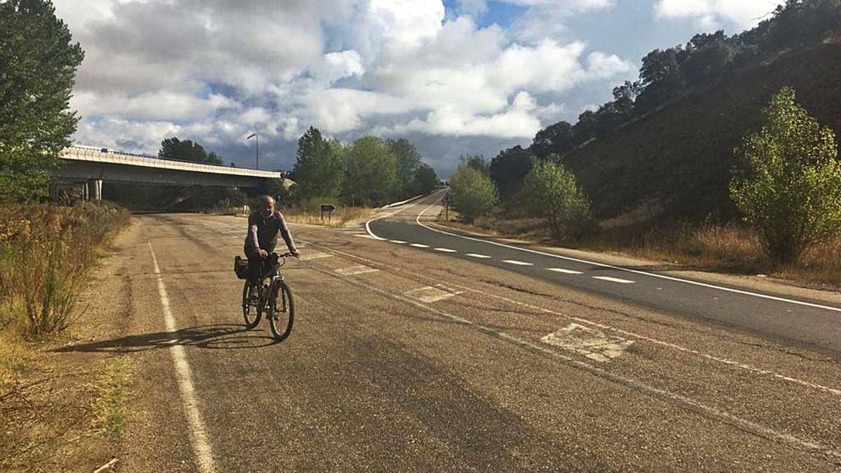 Un ciclista pasa a la altura del carril de incorporación a la A-52 en Villabrázaro, recientemente reparado.| J. A. G.