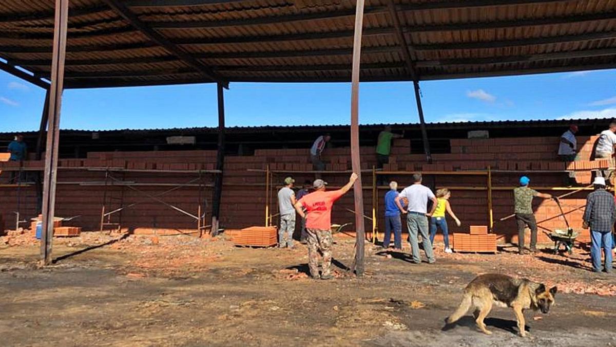 Trabajos de reconstrucción, ayer por la mañana, de la pared de la perrera en la explotación de Vegalatrave afectada por el incendio forestal
