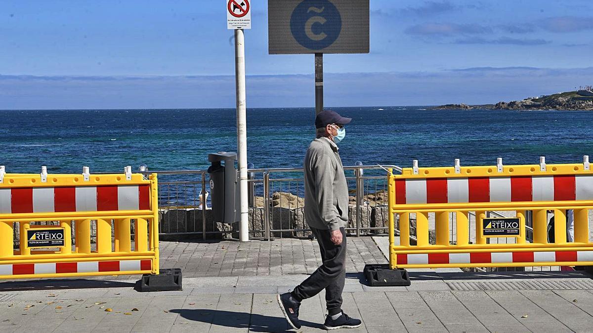Un ciudadano camina ante las vallas instaladas en los accesos a la playa. |   // CARLOS PARDELLAS