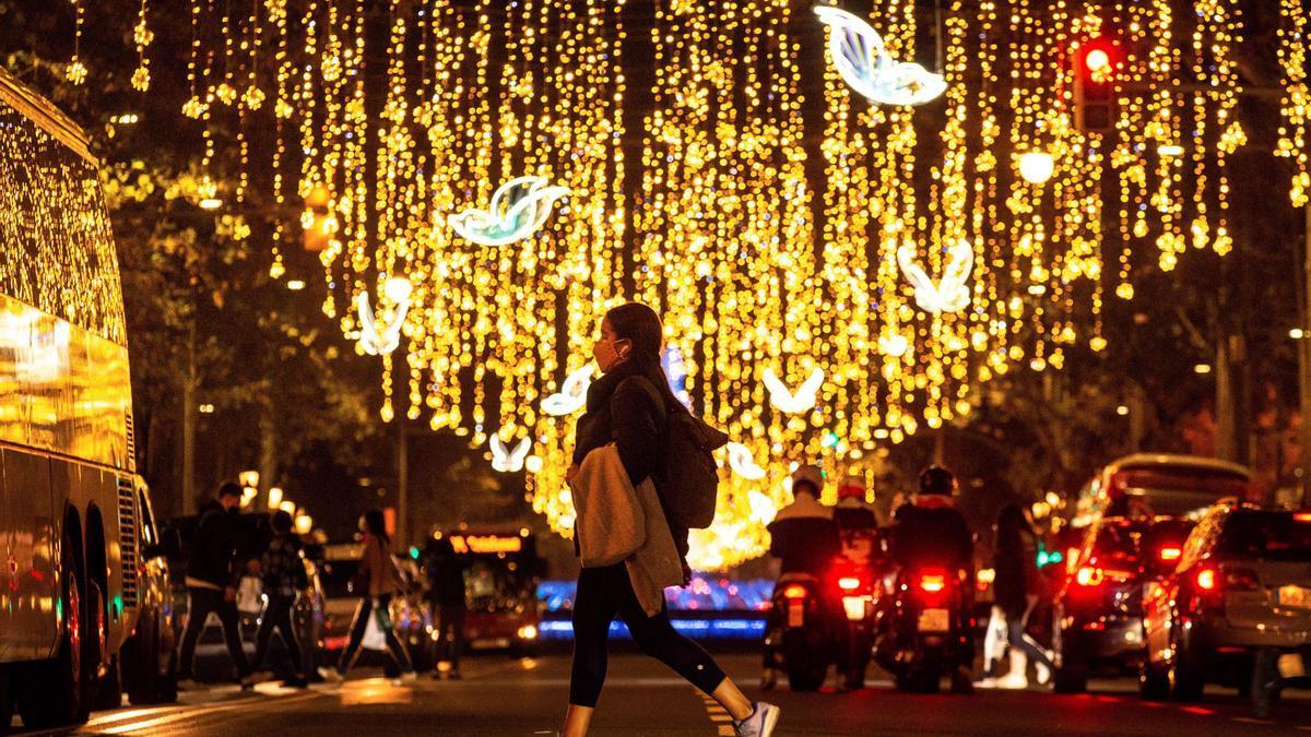 Una joven camina bajo la iluminación navideña.
