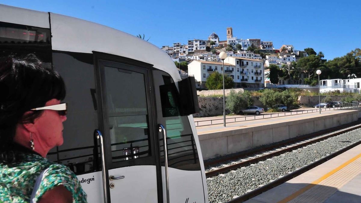 Una pasajera pasa junto a una un tranvía de la Línea 1 del  TRAM