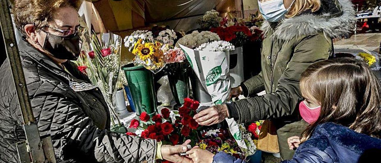 Adelaida Bedia, vendiendo flores a Isabel Menéndez, con su hija, Sofía Álvarez.