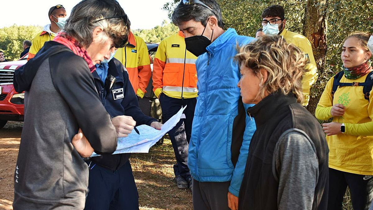 Un bomber indica a un grup de voluntaris la zona on han de fer una batuda per trobar el nen | ARNAU VALVERDE