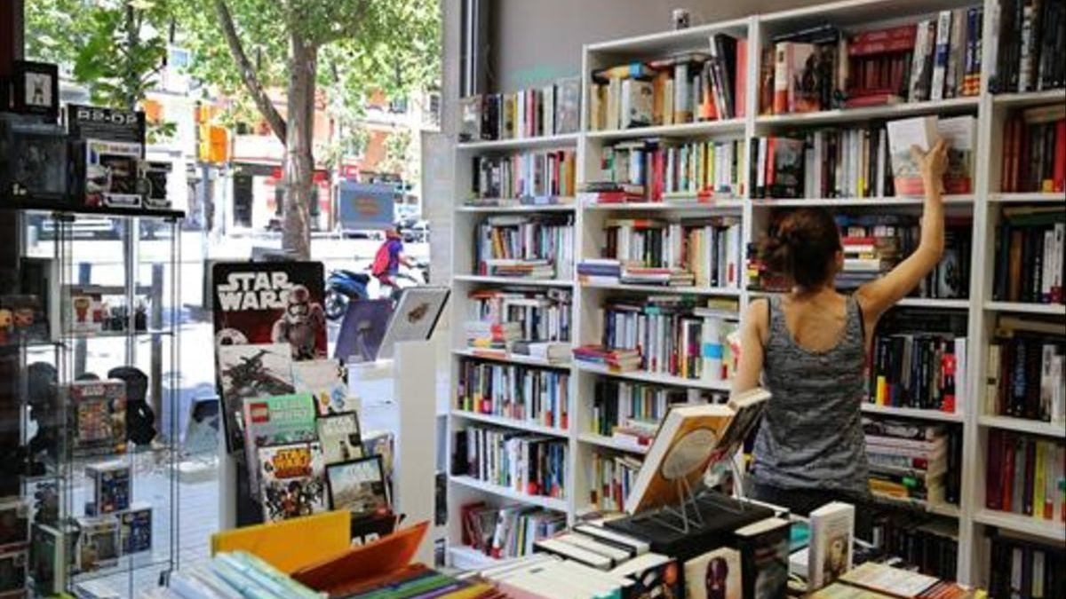 A young woman consults a work in a bookstore.