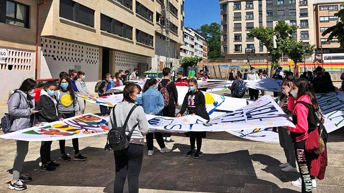 El alumnado del IES Ribeira do Louro trasladando las telas que dan forma al gran mural.   | // D.P.