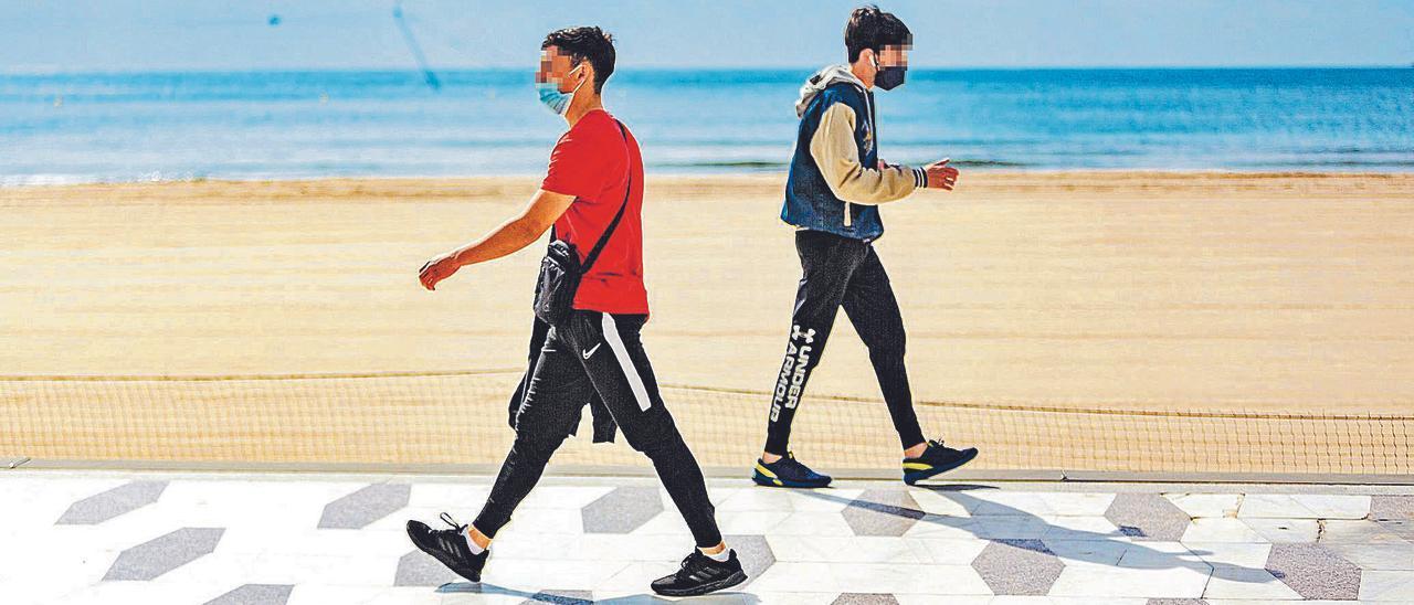 Dos jóvenes cruzan sus caminos en primera línea de playa, algo que se ha convertido en rutina para muchos de los que han perdido el empleo.