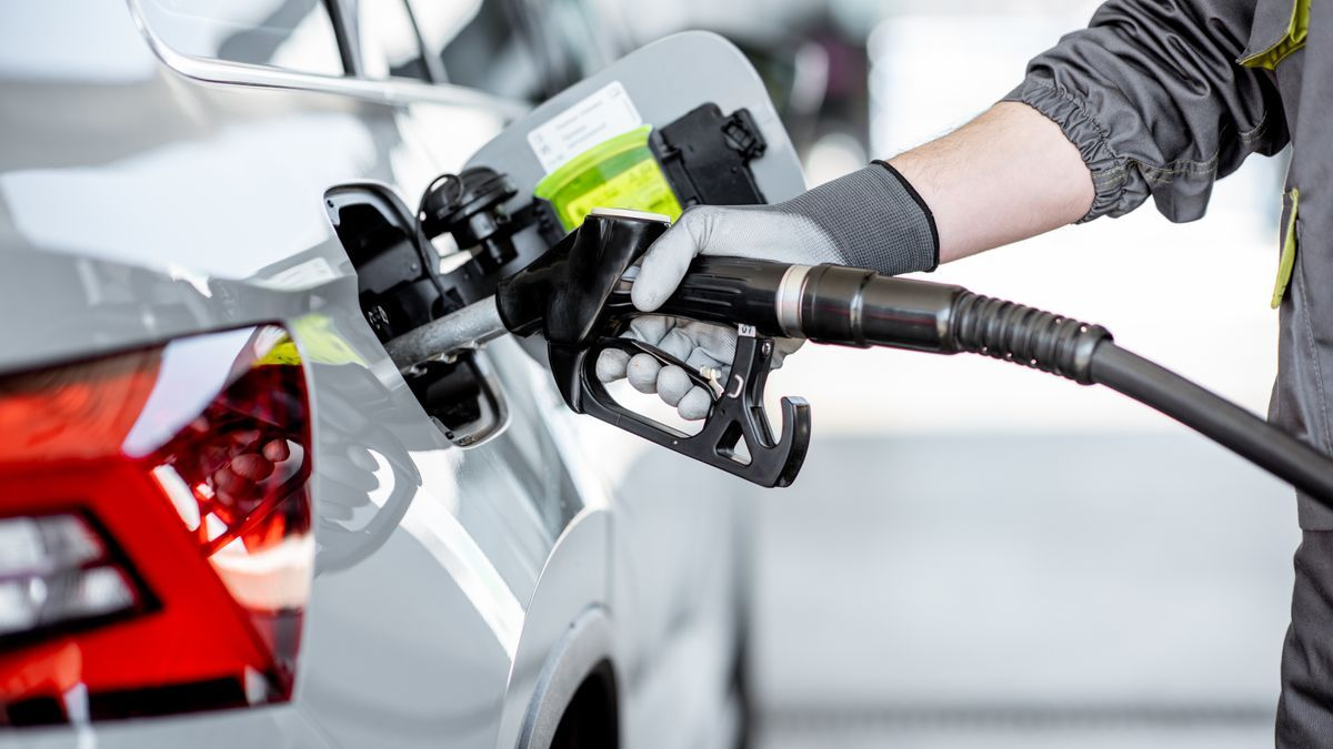 Un empleado de una gasolinera llenando el tanque de combustible de un coche