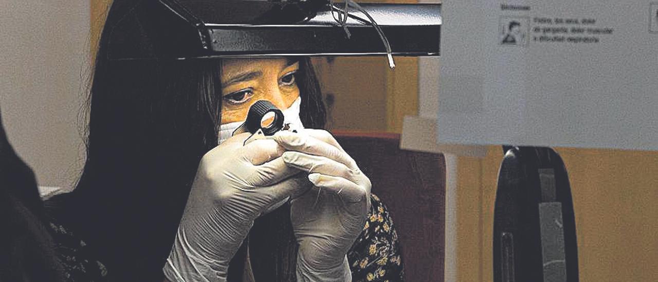 Una gemóloga analiza una pieza en un montepío local.