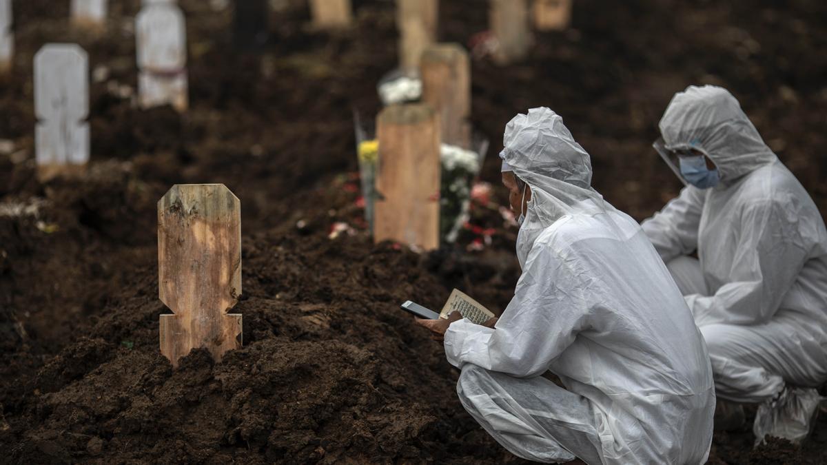 Familiares con equipos de protección velan a seres queridos muertos por covid en Indonesia