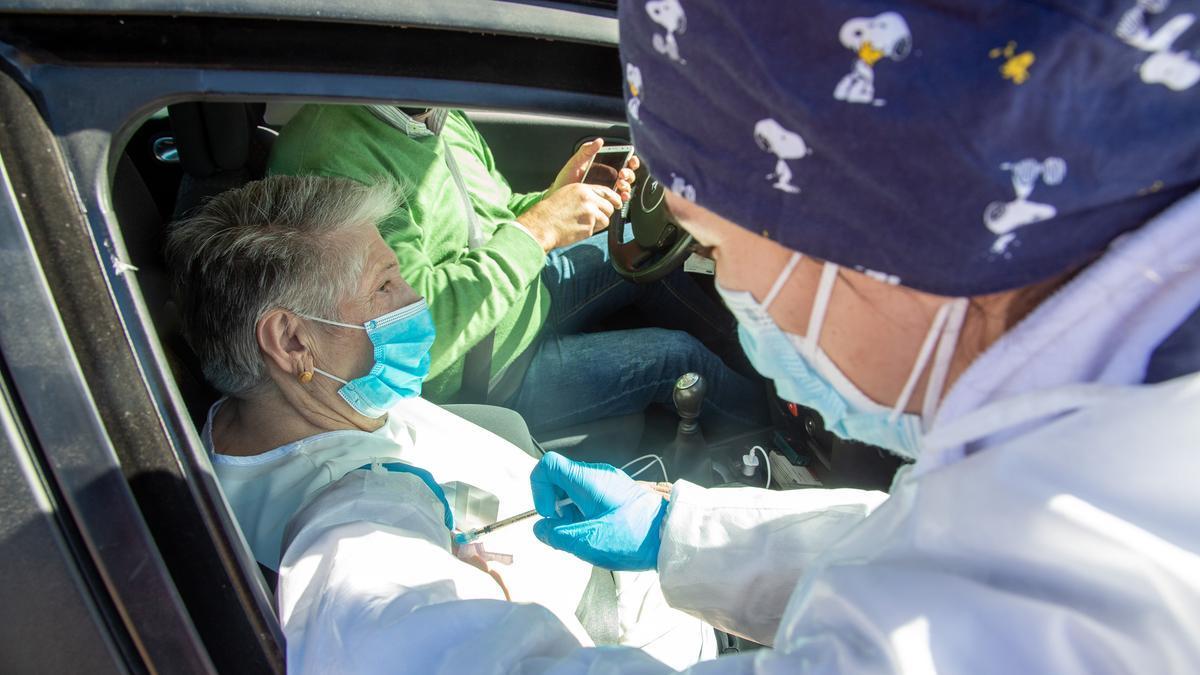 Una sanitaria inyecta la vacuna de Pfizer a una persona mayor que espera en el coche.