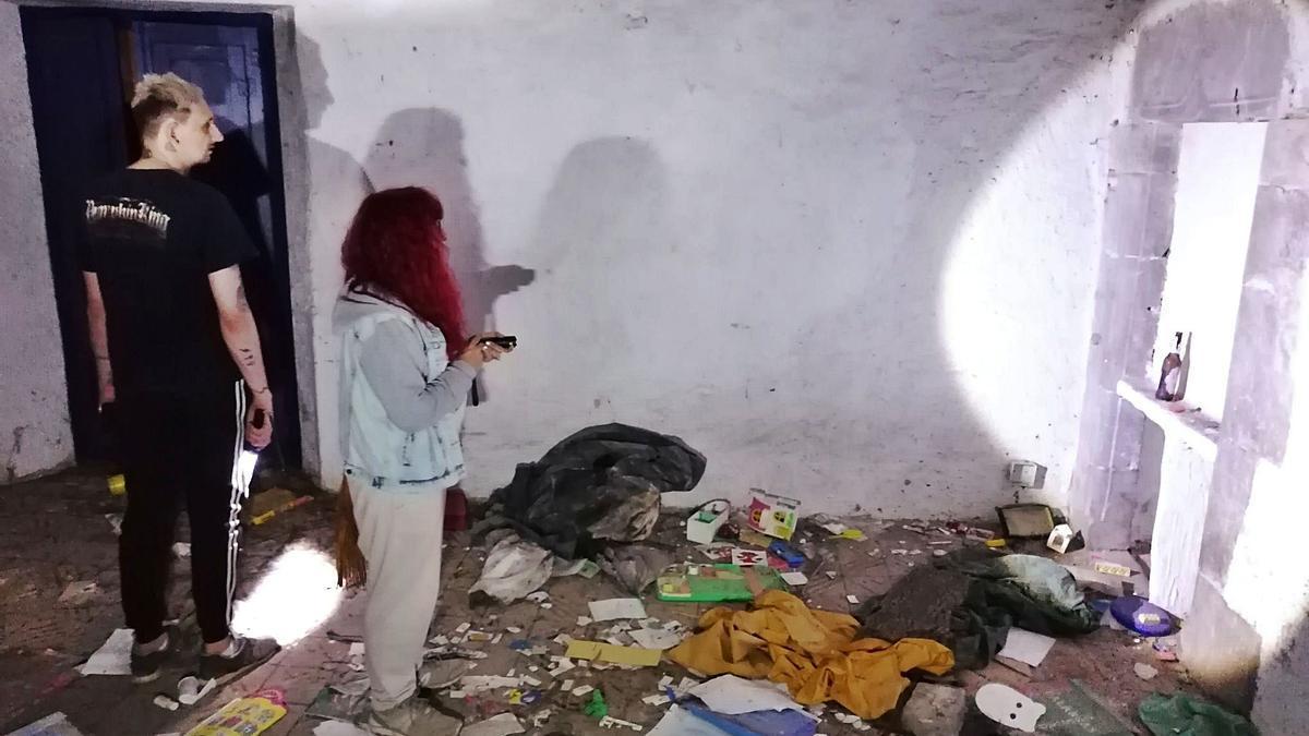 visita nocturna a una «casa embruixada» de Llers. 1 Sílvia Tresserras i José Garrido observen una paret de la masia; el terra és ple d'objectes. F  | MATÍAS CROWDER