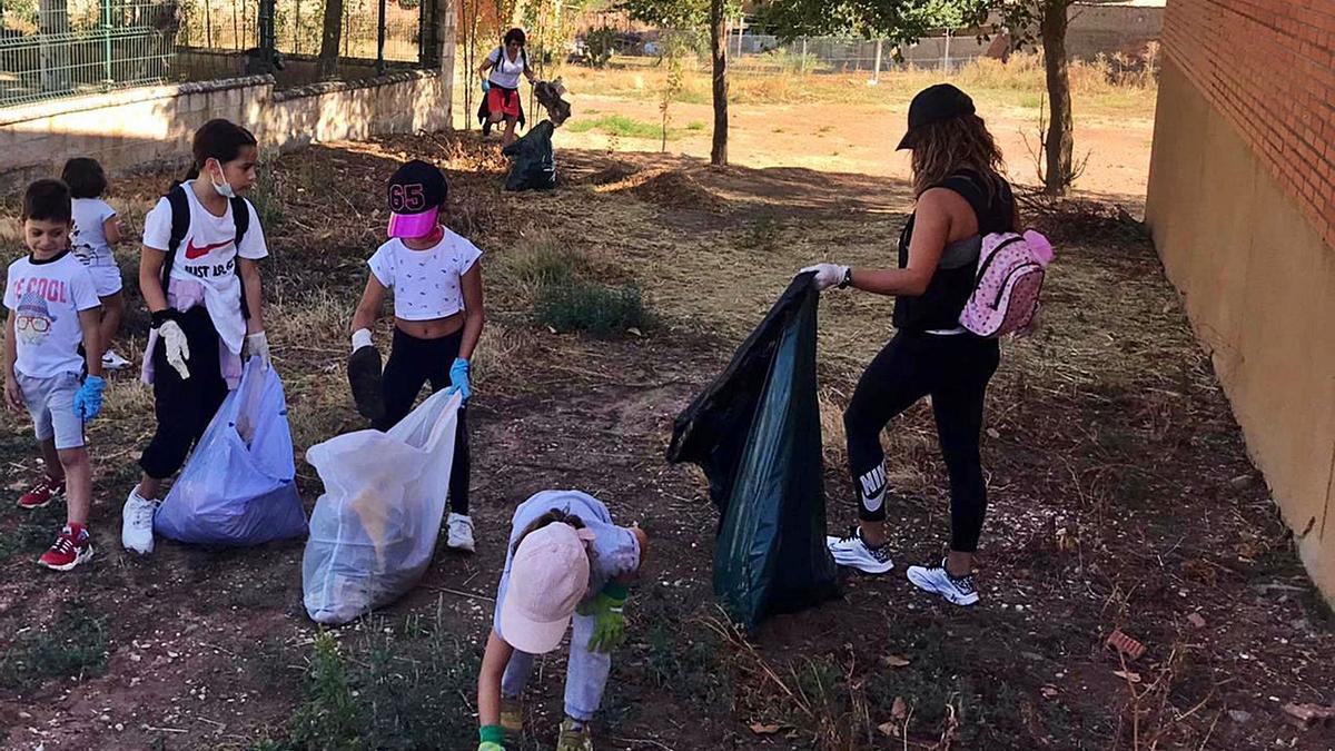 A la izquierda varios niños participan en la jornada de limpieza realizada en Andavías. Arriba voluntarios que han participado en la limpieza de las calles. y bolsas de basura recopiladas por los vecinos..      D. P.