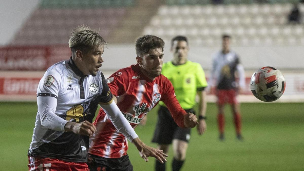 Benjamín Garay, nuevo fichaje rojiblanco, pelea con Escudero por hacerse con el balón en el Ruta de la Plata.   E. F.