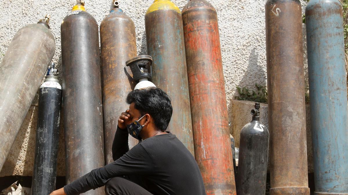 Un hombre se lamenta frente a bombonas de oxígeno vacías en India