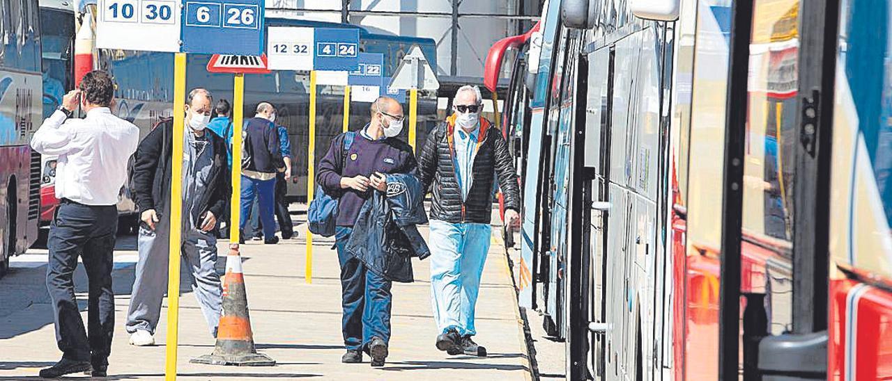 Trabajadores de Ford, en la terminal de autobuses de la factoría de Almussafes, tras acabar su turno.