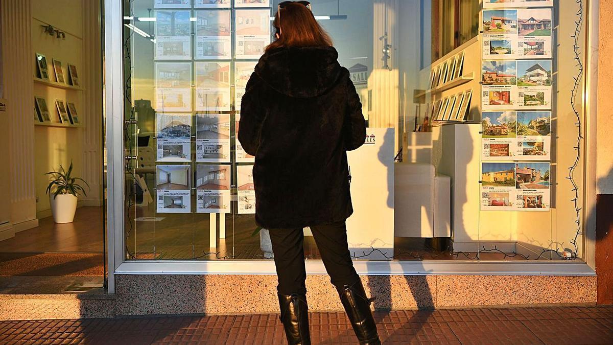 Una mujer observa los anuncios en una inmobiliaria.     // CARLOS PARDELLAS