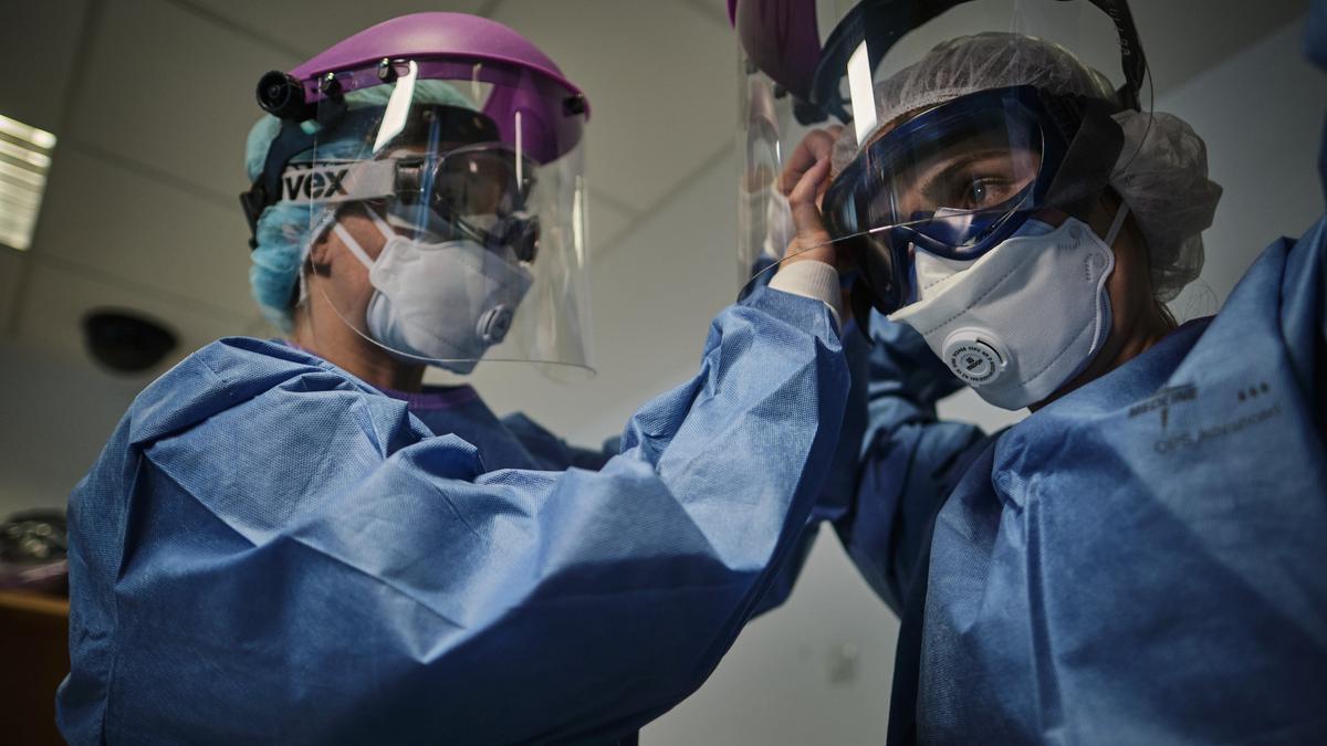 Dos sanitarios se colocan sus equipos de protección frente al Covid.