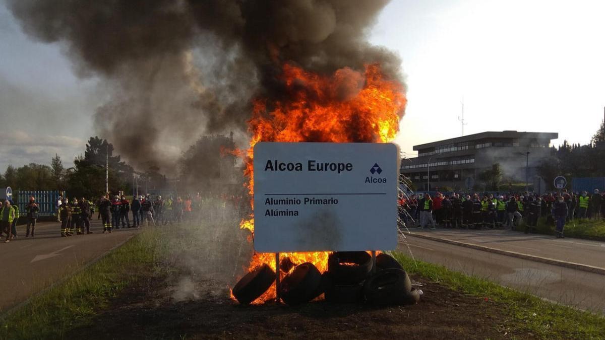Trabajadores de Alcoa protestan hoy delante de la fábrica quemando neumáticos. // Europa Press