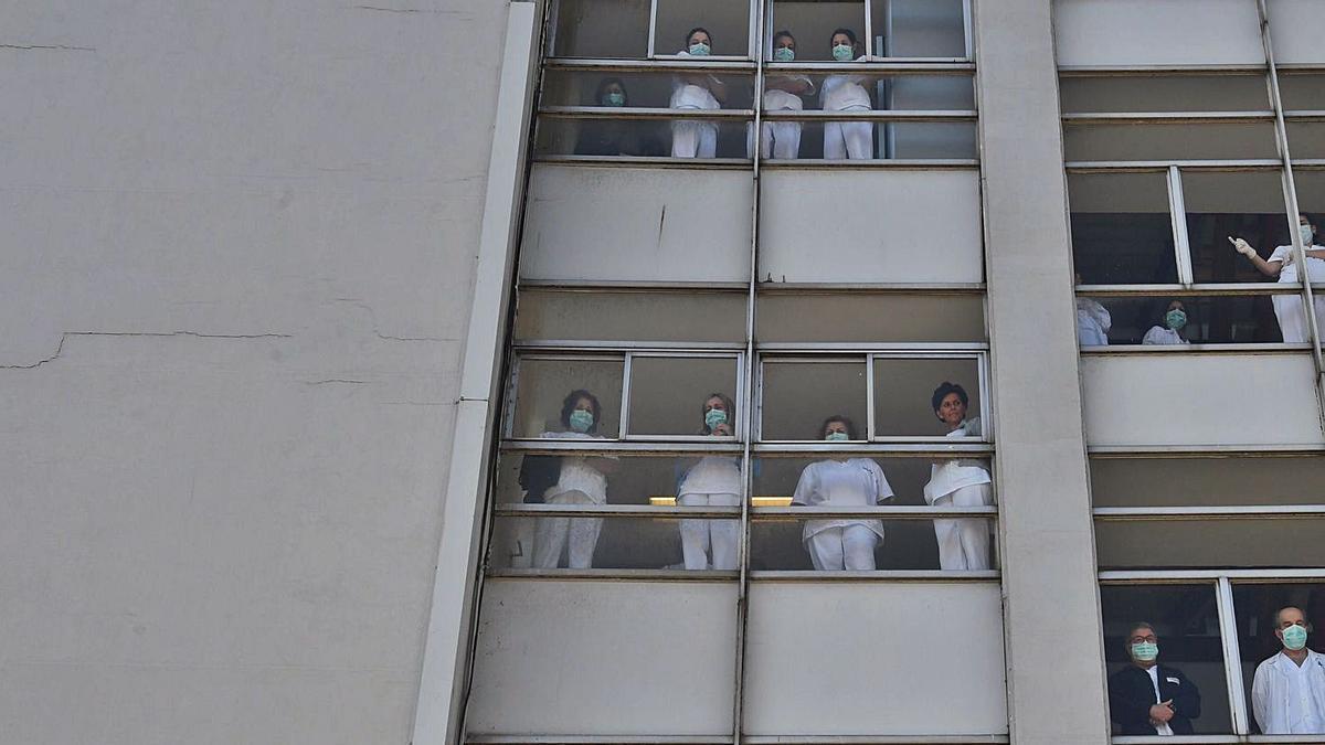 Sanitarios saludan desde las ventanas del Chuac en un homenaje tras el inicio de la pandemia.    // CARLOS PARDELLAS