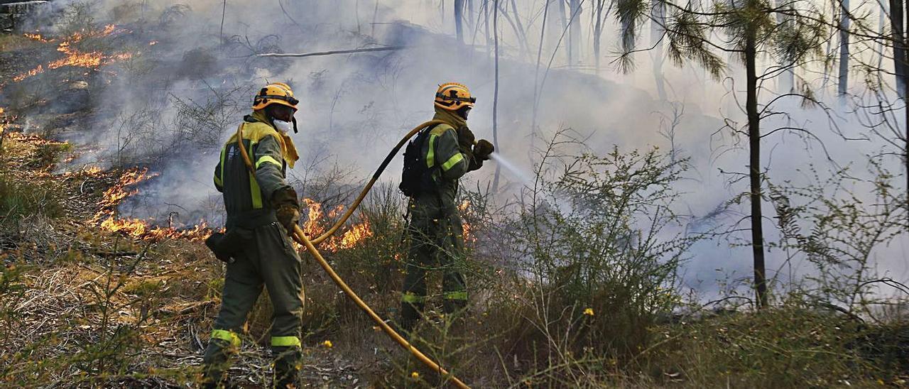 Efectivos contraincendios combaten el fuego en un monte de Soutomaior, en agosto de 2016. |   // ALBA VILLAR
