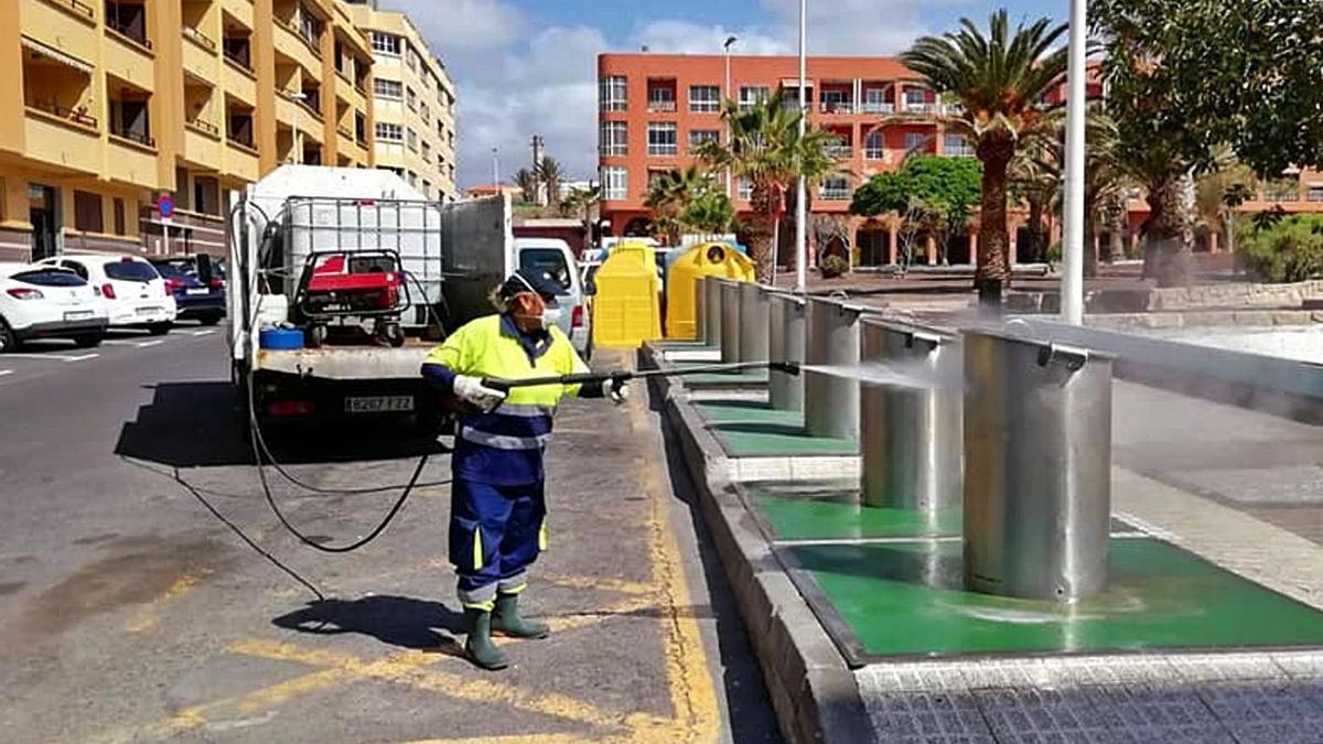 Un operario limpia los contenedores de basura soterrados en El Médano.     E.D.