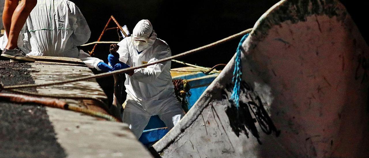Miembros de Salvamento sacan en el puerto de La Restinga los cadéveres de los inmigrantes del cayuco rescatado el domingo al sur de El Hierro . | | REUTERS / BORJA SUÁREZ