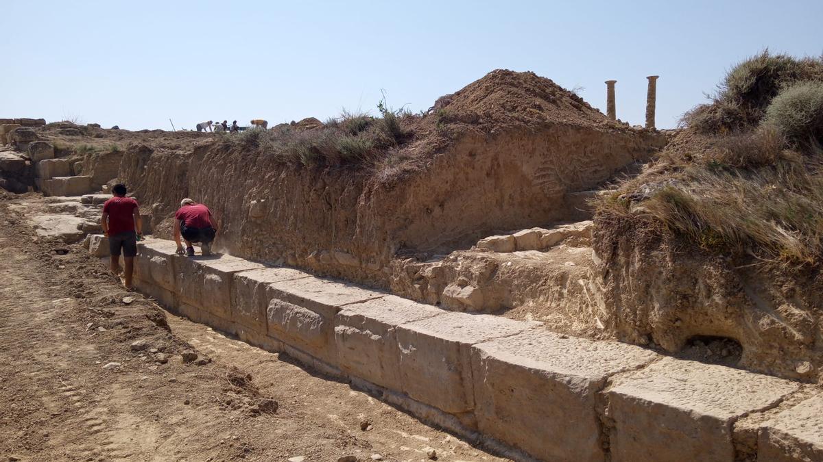 Dos estudiantes limpian los restos de lo que sería la muralla que cerraba la ciudad romana de Los Bañales.