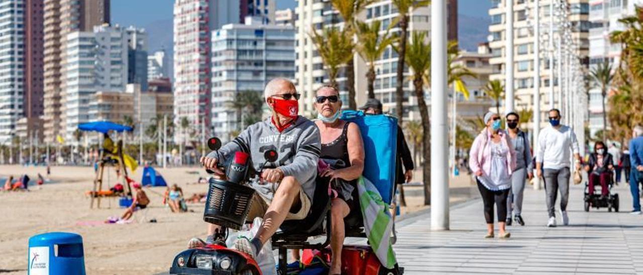 Una pareja de turistas británico circula por el paseo de Levante de Benidorm en un carrito eléctrico el pasado febrero.