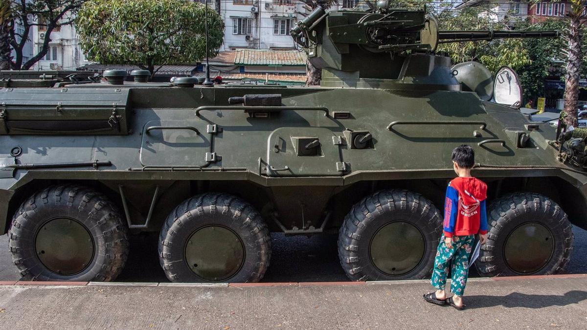 Un niño juega junto a un vehículo militar en Rangún.