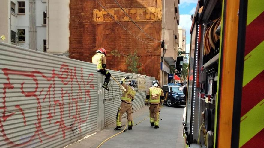 Los bomberos saltan una valla para apagar un incendio en Lorca