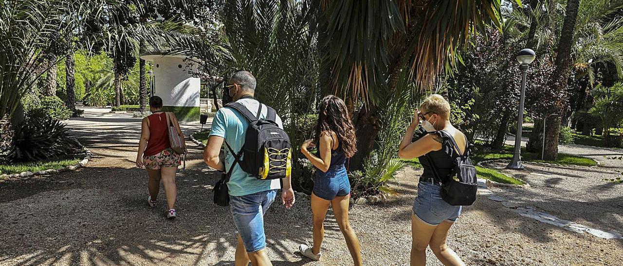 Un grupo de turistas pasean por el Parque Municipal de Elche junto a una guía.   ANTONIO AMORÓS