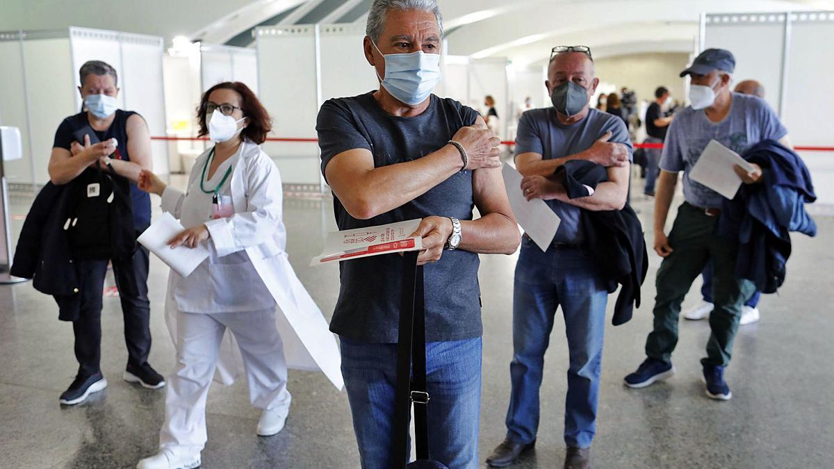Tres hombres presionan con el algodón sobre la zona en la que recibieron el pinchazo contra el coronavirus, ayer.  | M.A. MONTESINOS