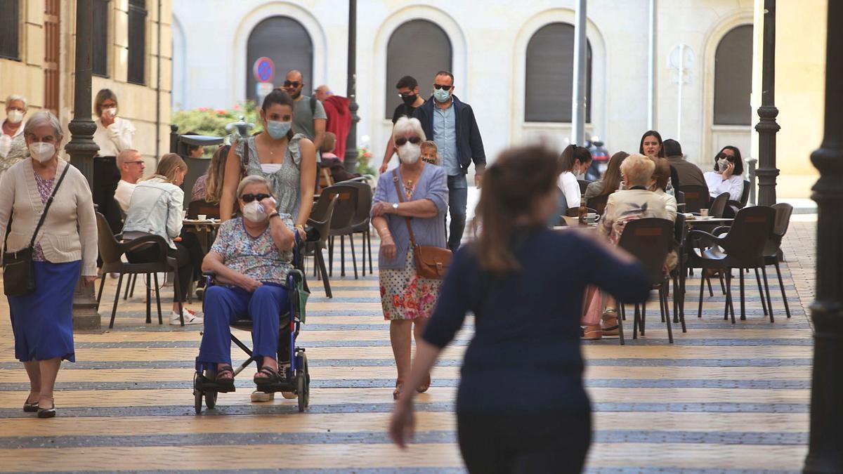 Varias personas de avanzada edad pasean por una de las calles céntricas de Alicante, mientras que pequeños grupos disfrutan en las terrazas.