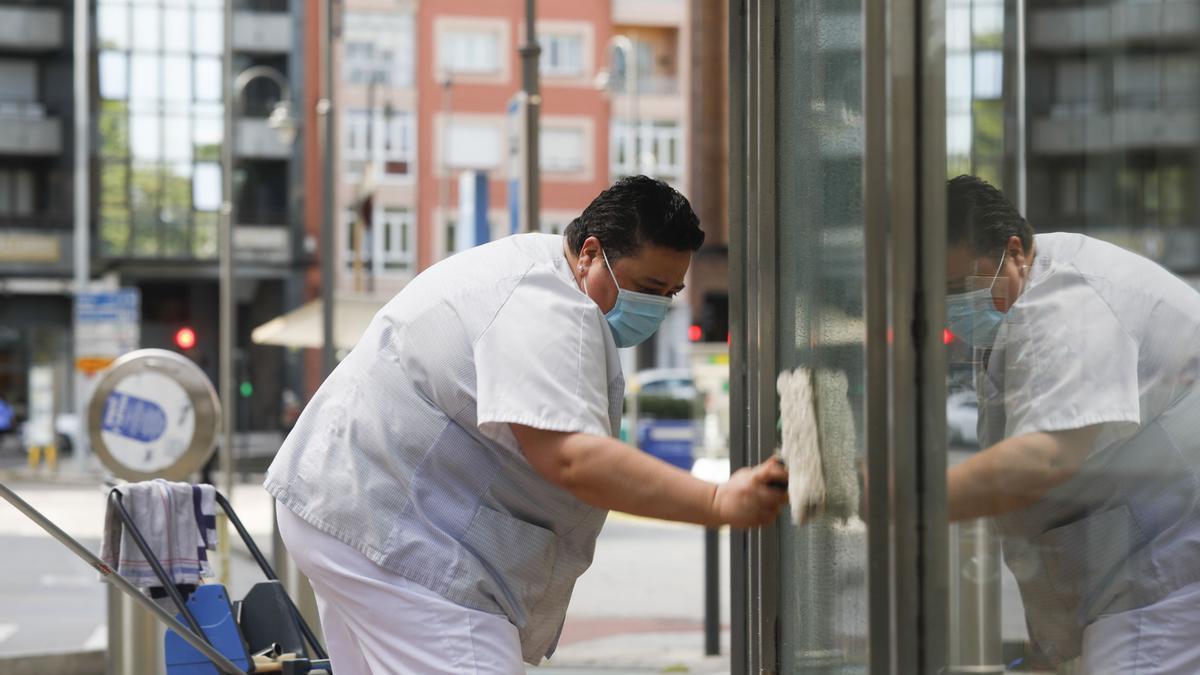 Una trabajadora limpia las lunas de un negocio.