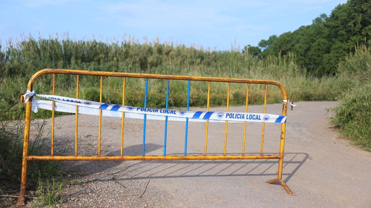 Una valla con precinto de la Policía Local cierra el acceso al Clot de Burriana donde apareció el cuerpo.
